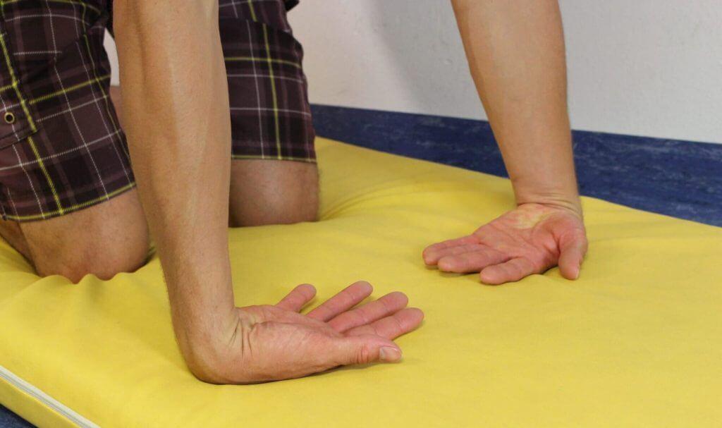 Handrücken am Boden als Dehnung